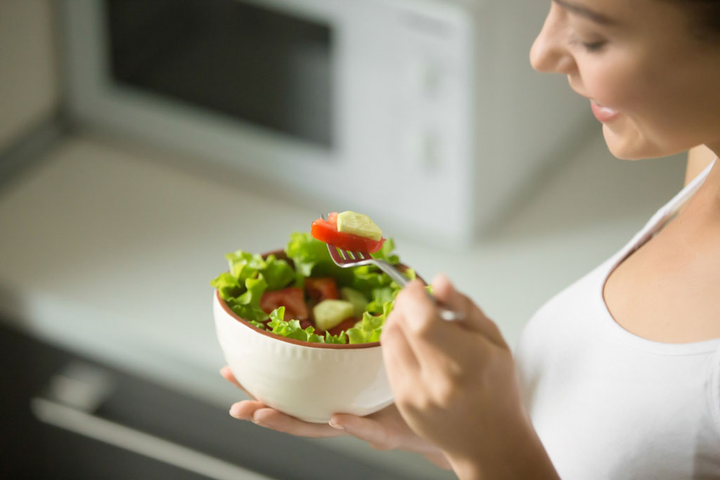 image showing a woman eating a green salad to boost their immunity | Agrrro