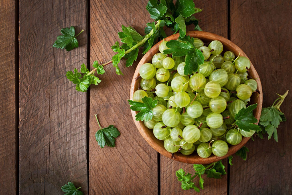 image showing amla or green gooseberries in a wooden bowl | Agrrro