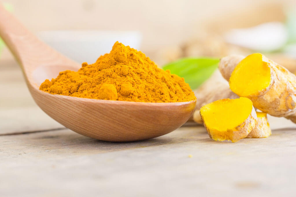 image showing turmeric and turmeric powder in a wooden spoon | Agrrro