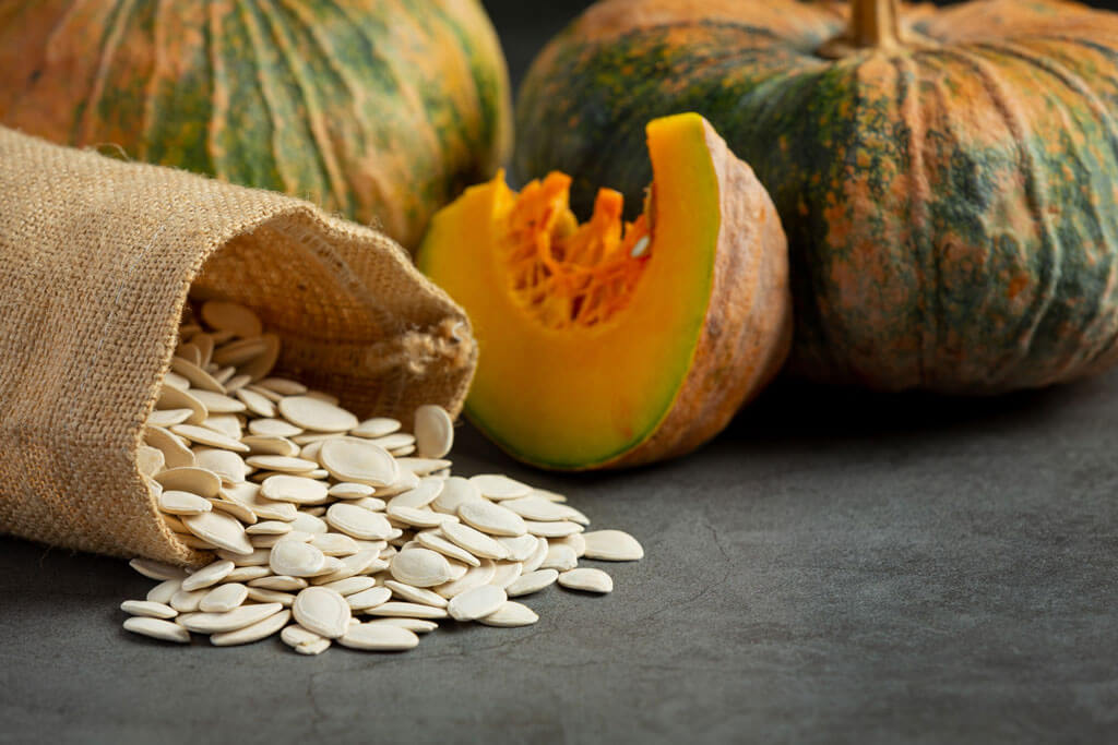 image showing pumpkin seeds and pumpkin in the background   Agrrro