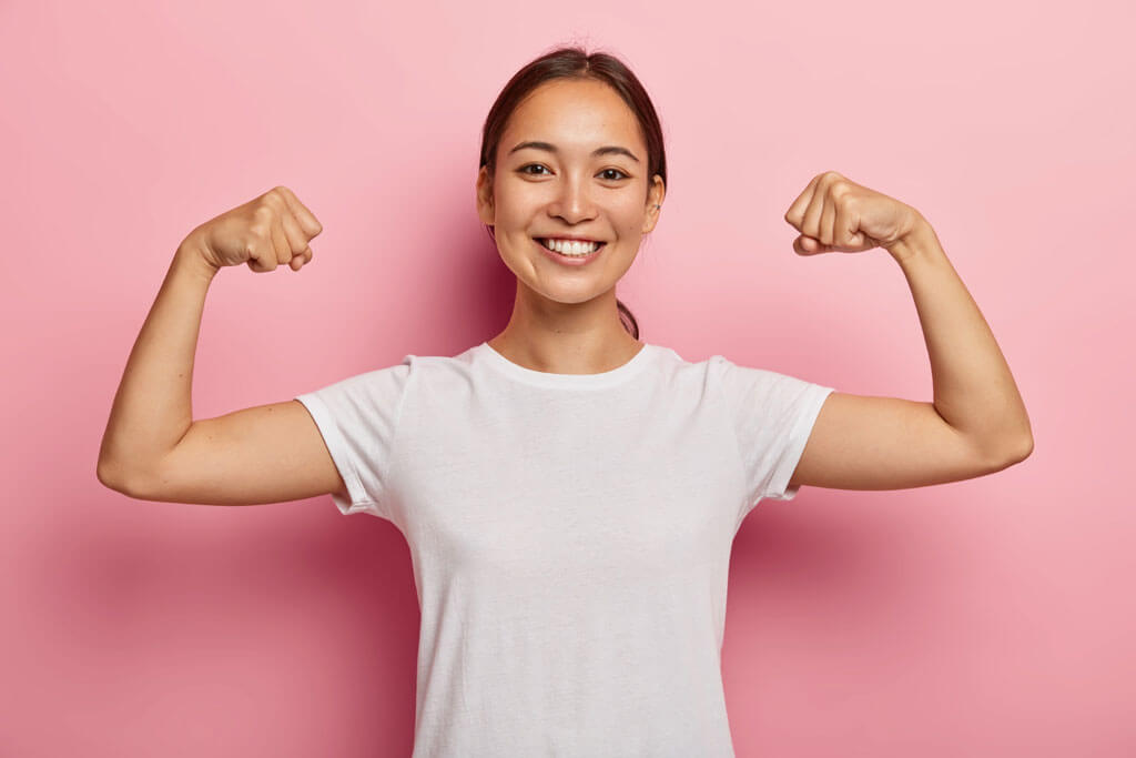 a woman showing biceps to present the health benefits of organic food | Agrrro