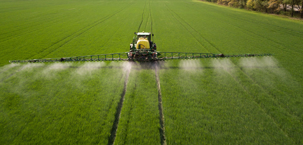 image shwoing the tractor spraying pesticides and chemical fertilizers in the fields | Agrrro